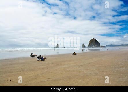People riding recumbent beach bikes near Haystack Rock in Cannon Beach, Oregon. Oregon Coast, USA - Stock Photo