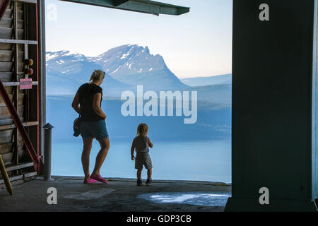 mother and child silhouette, looking out of cable-car station - Stock Photo