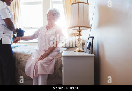 Indoors shot of happy senior woman sitting on bed with female nurse checking blood pressure. Home caregiver testing - Stock Photo