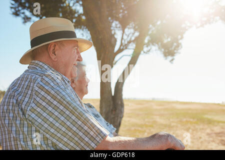 Side view shot of senior man in hat sitting outdoors with his wife and enjoying a view. Elderly couple relaxing - Stock Photo