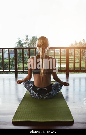 Rear view shot of young woman sitting in lotus yoga pose on exercise mat. Fitness female model doing meditation - Stock Photo