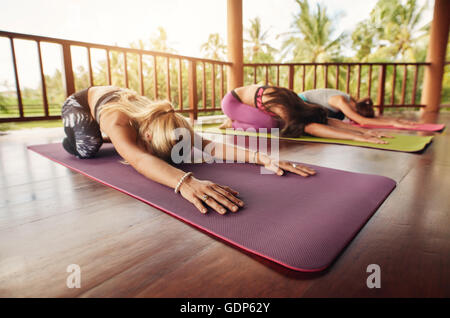 women practicing yoga together and sitting in the lotus