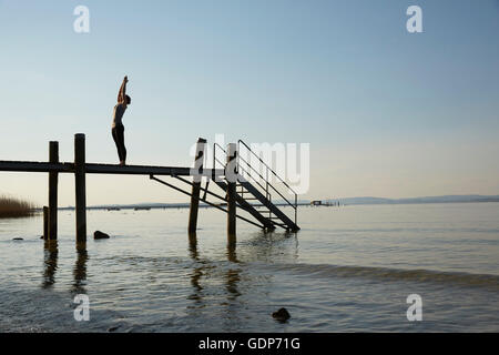 Silhouette of woman on pier arms raised in yoga position - Stock Photo