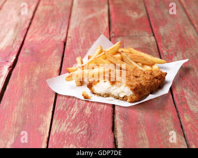 Food, fish, breaded cod and chips on rustic red painted wood - Stock Photo