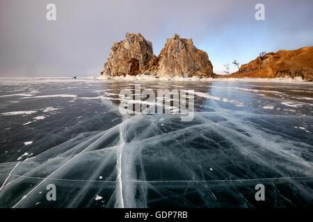 View of frozen ice and Shamanka Rock on Burkhan Cape, Baikal Lake, Olkhon Island, Siberia, Russia - Stock Photo