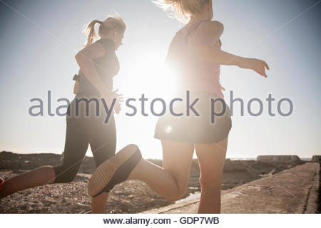 Two young female runners running along sunlit coast, Seapoint, Cape Town, South Africa - Stock Photo