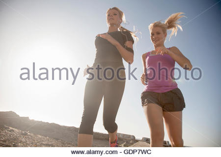 Two young female runners running at coast, Seapoint, Cape Town, South Africa - Stock Photo