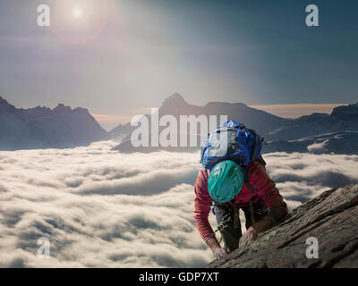 Climber on a rocky wall above a sea of fog in an alpine valley, Alps, Canton Wallis, Switzerland - Stock Photo