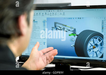 Engineer works with CAD design imagery in racing car factory, close up - Stock Photo