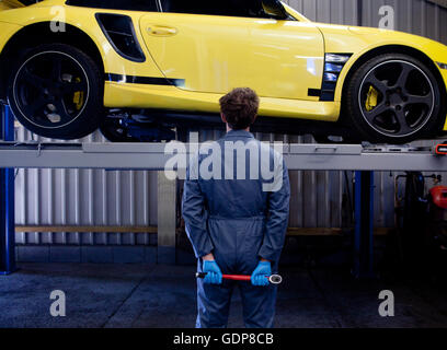 Male mechanic checking yellow sports car, holding socket wrench behind his back, rear view - Stock Photo