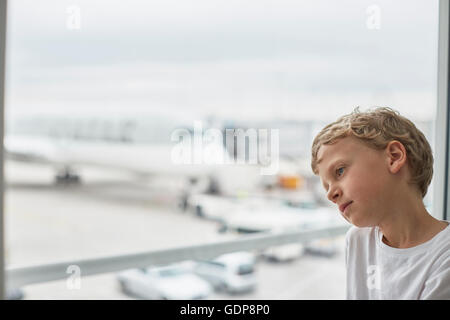 Boy looking out of airport window - Stock Photo
