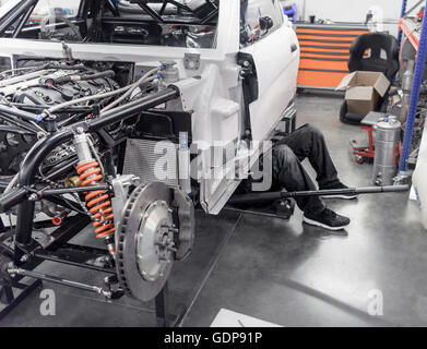 Engineer working under car in racing car factory - Stock Photo