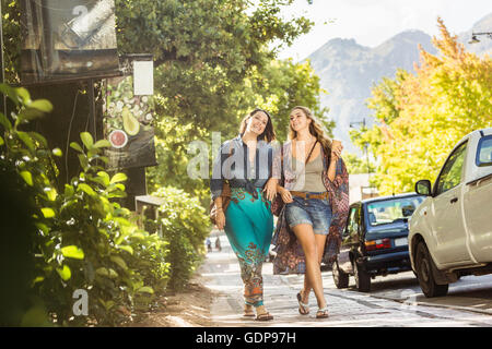 Two women friends strolling on roadside  arm in arm, Franschhoek, South Africa - Stock Photo