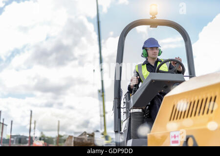 Apprentice builders training with road roller on building site - Stock Photo