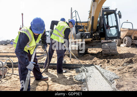 Apprentice builders laying concrete foundations on building site - Stock Photo