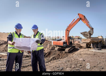 Apprentice builders studying drawings on housing building site - Stock Photo