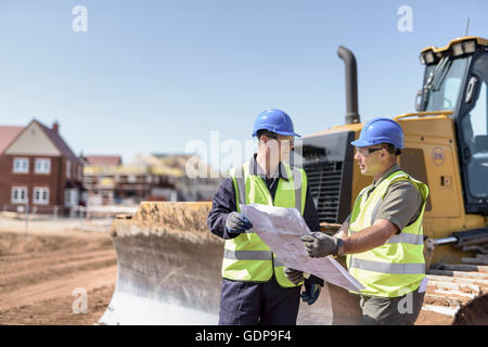 Builders discussing site drawings on housing building site - Stock Photo