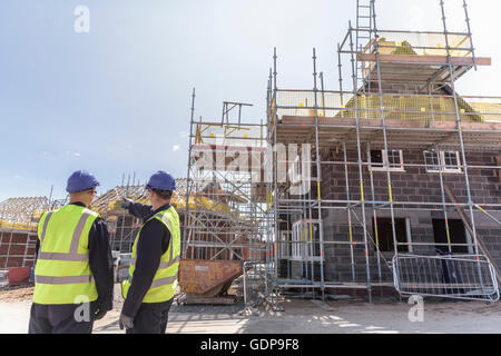 Builders discussing housing development on building site - Stock Photo
