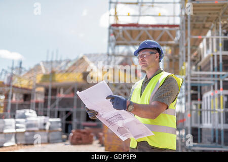 Site manager looking at plans on housing building site - Stock Photo