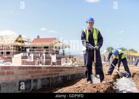 Portrait of apprentice builder laying pipework on housing building site - Stock Photo