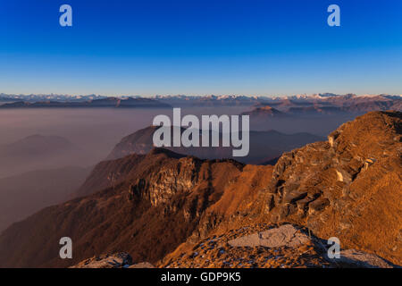 Elevated misty landscape with distant snow capped mountains, Monte Generoso,Ticino, Switzerland - Stock Photo