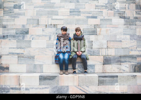 Two sisters sitting together on steps - Stock Photo