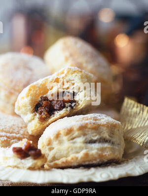 Puff pastry minced pies, dusted with icing sugar, on vintage plate, christmas fairy lights in background - Stock Photo