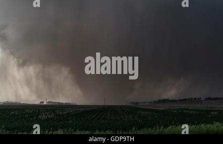 A violent, rain-wrapped wedge tornado rips up farmland in rural Kansas - Stock Photo