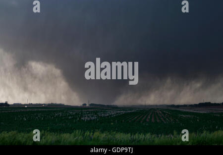 A violent, rain-wrapped wedge tornado rips up farmland in rural Kansas - Stock Photo