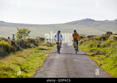 Front view of cyclists cycling on rural road - Stock Photo