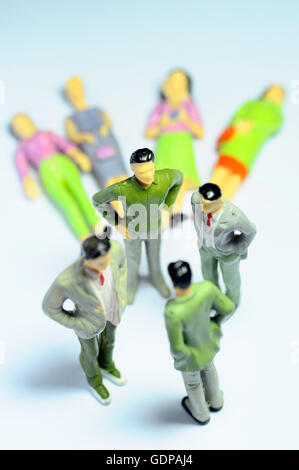 Figurines of businessman standing over women lying on ground - Stock Photo