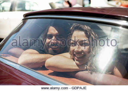 Young couple on road trip looking through vintage car back window, Cape Town, South Africa - Stock Photo