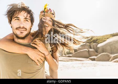 Woman getting running piggy back from boyfriend at beach, Cape Town, South Africa - Stock Photo
