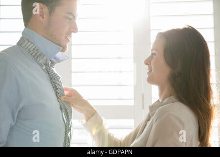 Young businesswoman fastening business boyfriends tie - Stock Photo