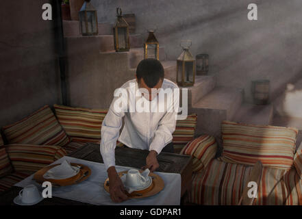 Waiter preparing place settings, Marrakesh, Morocco - Stock Photo