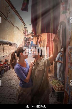Young couple at market, Jemaa el-Fnaa Square, Marrakesh, Morocco - Stock Photo