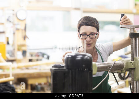 Woman in workshop using machinery - Stock Photo
