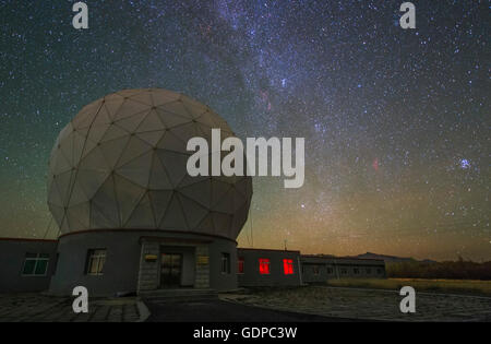 The Milky Way from Cassiopeia to Auriga appears over the Delinha observatory in Qinghai province of China. The dome, - Stock Photo