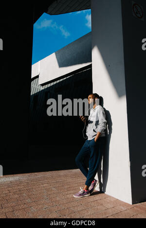 Young woman wearing earphones standing leaning a wall looking away confidently. Fitness female taking break for - Stock Photo