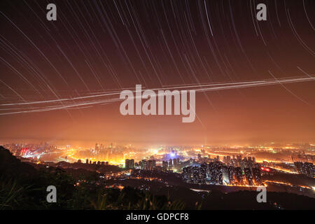Stars appear above city lights on this clear night after the rain. This 3-hour exposure was taken from the top of - Stock Photo