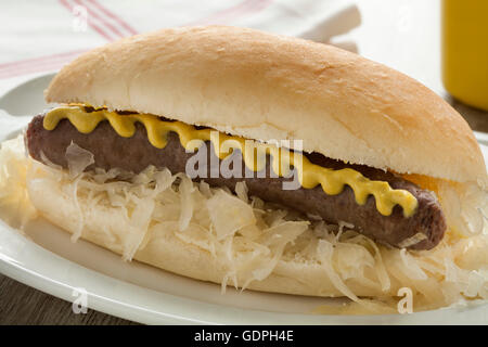 White bun with sauerkraut, sausage and mustard close up - Stock Photo