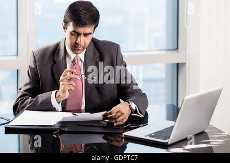 Indian Senior Executive in his skyscraper office, reading business contracts - Stock Photo