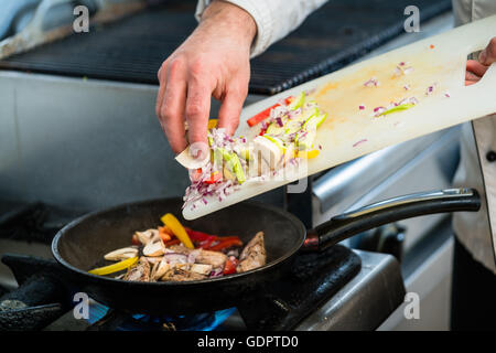 Chef putting ingredients to pan on cooker in restaurant kitchen - Stock Photo