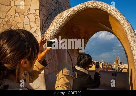 Tourists taking pictures of Sagrada Familia, from rooftop of Casa Mila, La Pedrera, Barcelona, Catalonia, Spain - Stock Photo