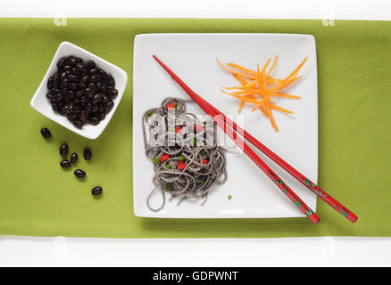 Black Bean and Black Bean Spaghetti garnished with Carrots - Stock Photo
