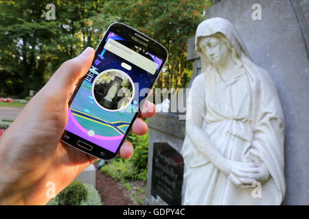 Pokémon go-player with his cellphone on a cemetery in Dortmund, Germany
