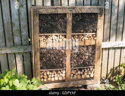 Insect or bug hotel on an allotment garden, made from recycled materials - Stock Photo