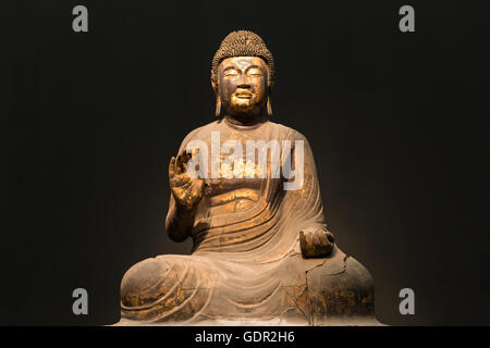 Statue of a sitting Buddha with golden painting - Stock Photo