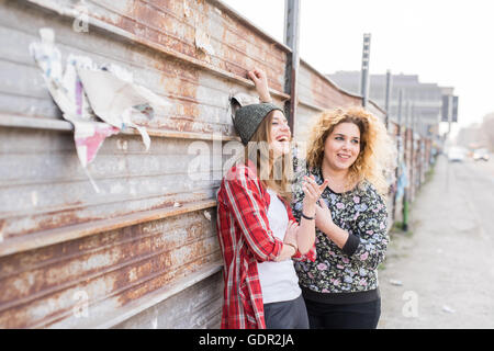 Half length of two young curly and straight blonde hair caucasian woman leaning against a wall of metal sheet, both - Stock Photo