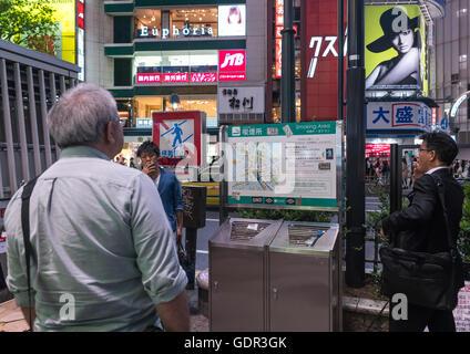Men in a outdoors public smoking area in shibuya, Kanto region, Tokyo, Japan - Stock Photo
